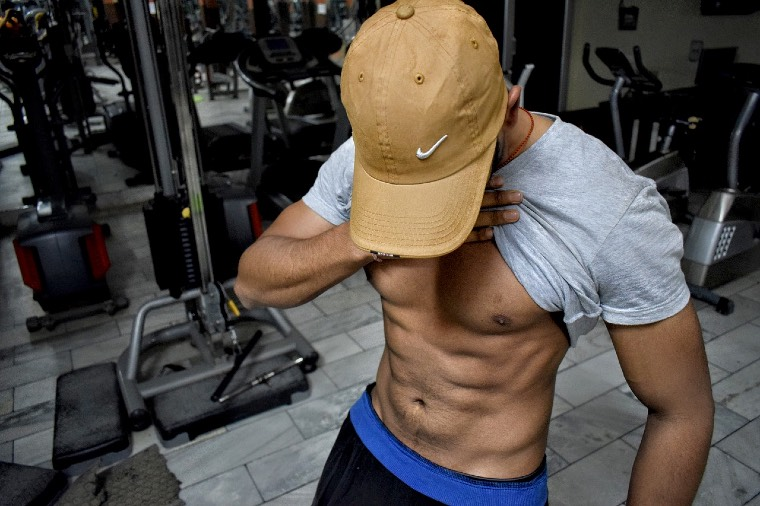 A man flexing his ripped abs in the gym